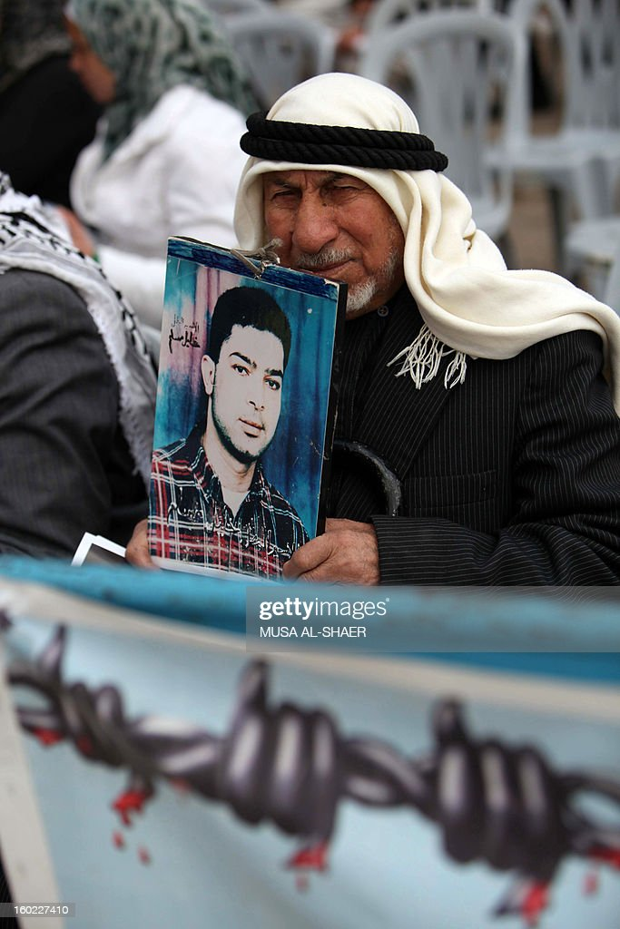 A Palestinian protestor holds a picture of a detained relative during a demonstration in support of Palestinians on a hunger strike in Israeli jails, in front of the Church of the Nativity at the West Bank city of Bethlehem on January 28, 2013.