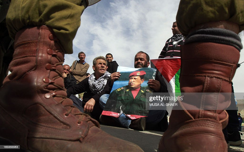 A Palestinian protestor holds a picture of late Venezuelan President Hugo Chavez during a weekly demonstration against Israeli occupation in the West Bank village of Maasarah near Bethlehem on March 8, 2013. Palestinians in Gaza and the West Bank were united in grief over the death of Venezuela's Hugo Chavez, whose untiring support for their cause saw him make blistering attacks on Israel. Placard in Arabic reads 'revolutionaries never die.' AFP PHOTO/MUSA AL-SHAER