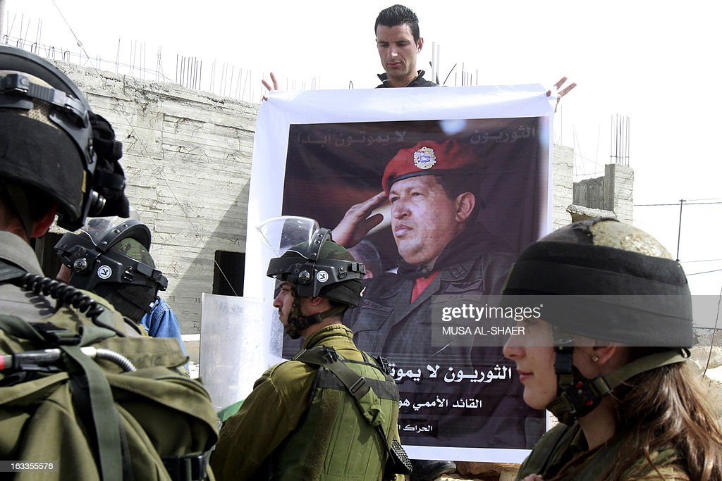 A Palestinian protestor holds a picture of late Venezuelan President Hugo Chavez during a weekly demonstration against Israeli occupation in the West Bank village of Maasarah near Bethlehem on March 8, 2013. Palestinians in Gaza and the West Bank were united in grief over the death of Venezuela's Hugo Chavez, whose untiring support for their cause saw him make blistering attacks on Israel. Placard in Arabic reads 'revolutionaries never die.'