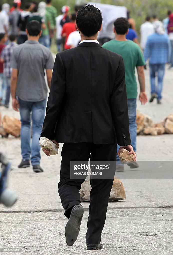A Palestinian protestor holds stones during clashes with Israeli security forces after they remove rocks from a makeshift road block on the road leading to the West Bank village of Deir Jarir, east of Ramallah on May 19, 2013 which Israeli soldiers closed off the previous day due to ongoing clashes with Palestinian demonstrators.