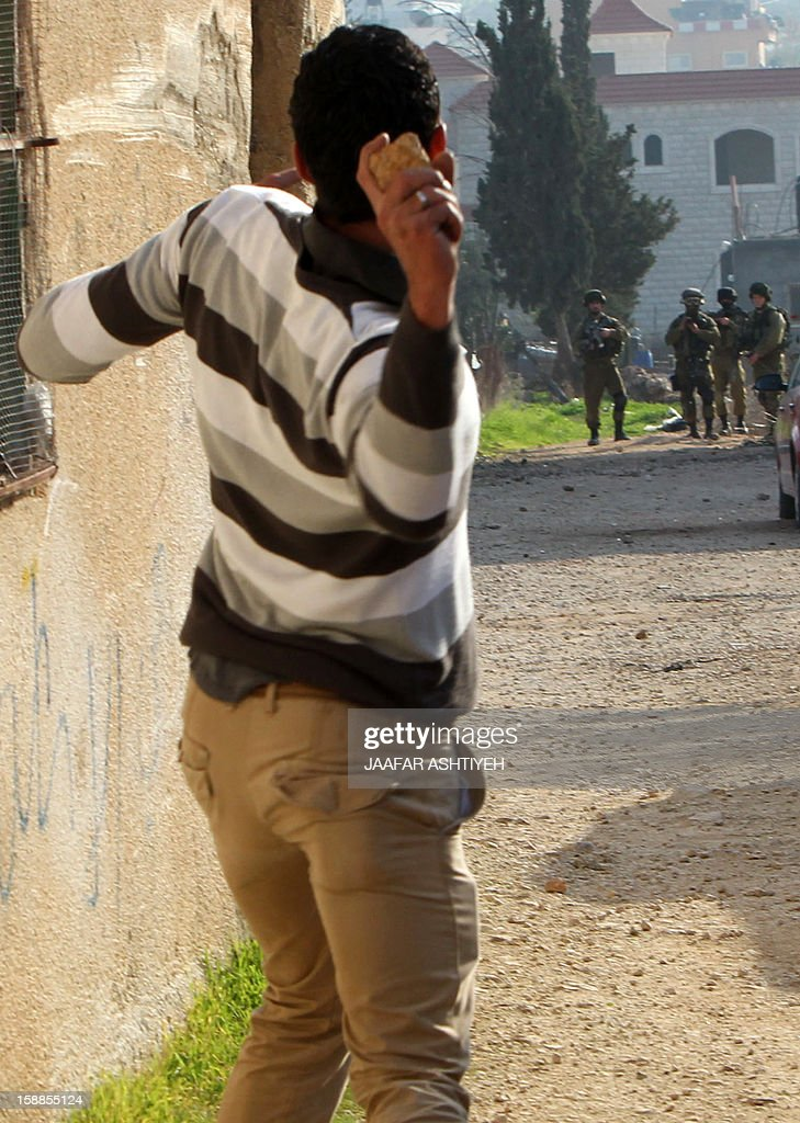 A Palestinian protestor hurls stones at Israeli security forces during clashes in the West Bank village of Tamoun, near Jenin on January 1, 2013. Israeli troops wounded dozens of Palestinians in clashes in a West Bank village after the discovery of a small commando force disguised as Arabs brought a crowd of stone-throwing villagers onto the streets, Palestinians said. AFP PHOTO / JAAFAR ASHTIYEH