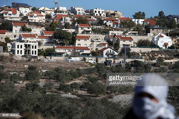 A Palestinian protestor is seen in front of the Israeli settlement of Qadumim during clashes with Israeli security forces following a demonstration...