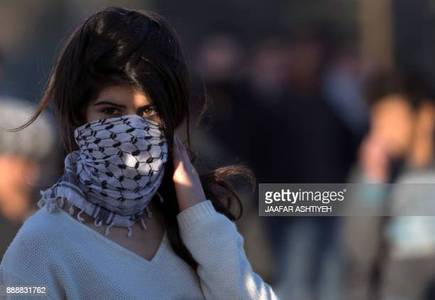 A Palestinian protestor looks on during clashes with Israeli security forces in the West Bank city of Nablus following a demonstration against US...