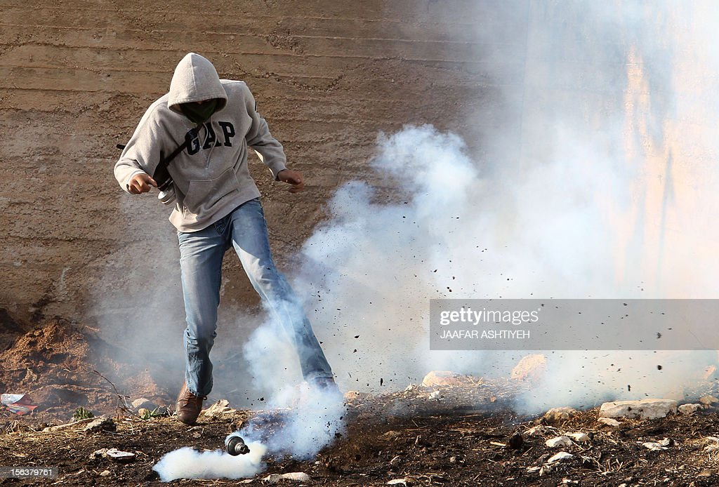 A Palestinian protestor reacts as a tear gas canister fired by Israeli forces lands next to him during clashes in the village of Kafr Qaddum, near the West Bank city of Nablus, on November 14, 2012. Palestinians held rallies across the West Bank, a day before the 24th anniversary of the Palestine Liberation Organisation's declaration of independence. PHOTO