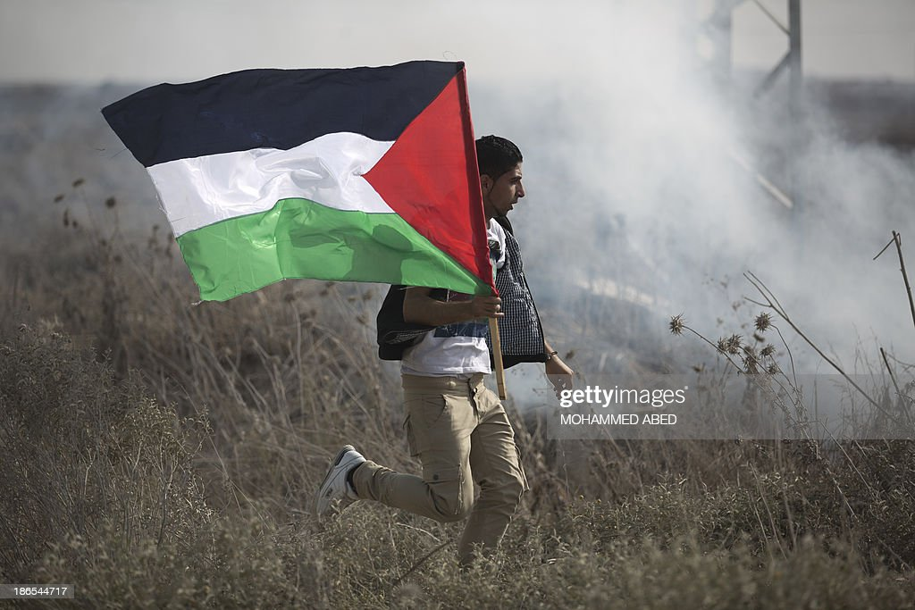 A Palestinian protestor runs with his national flag during clashes with Israeli forces following a protest near the Nahal Oz border crossing with Israel, east of Gaza City, on November 1, 2013. An Israeli raid to destroy a Gaza tunnel ignited clashes in which tank fire killed four Hamas commanders and five Israeli soldiers were wounded, officials from both sides said.