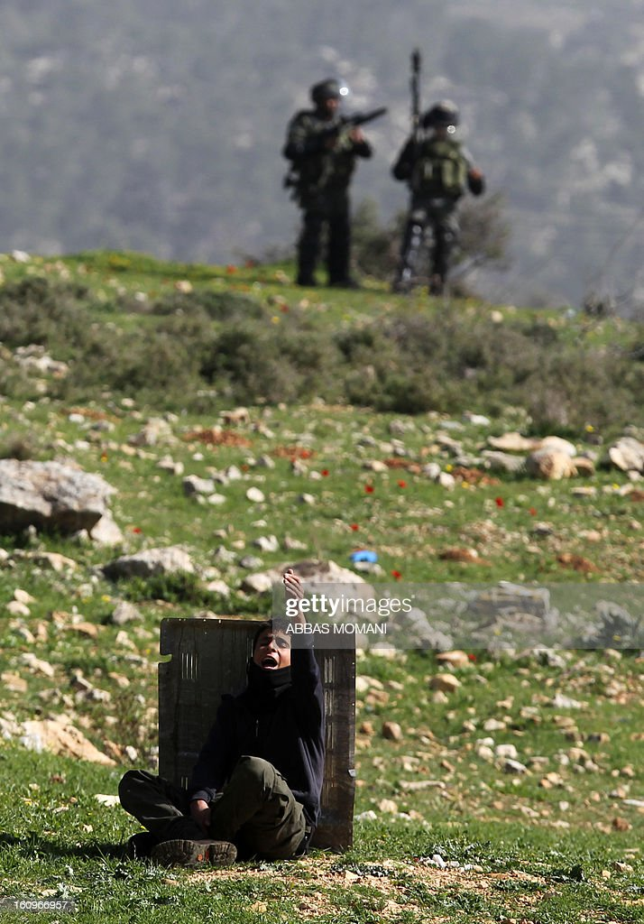 A Palestinian protestor takes cover behind a piece of metal as Israeli soldiers monitor during clashes following a demonstration organised by residents of the West Bank village Nabi Saleh to protest against the expansion of Jewish settlements on Palestinian land on February 8, 2013. AFP PHOTO/ABBAS MOMANI