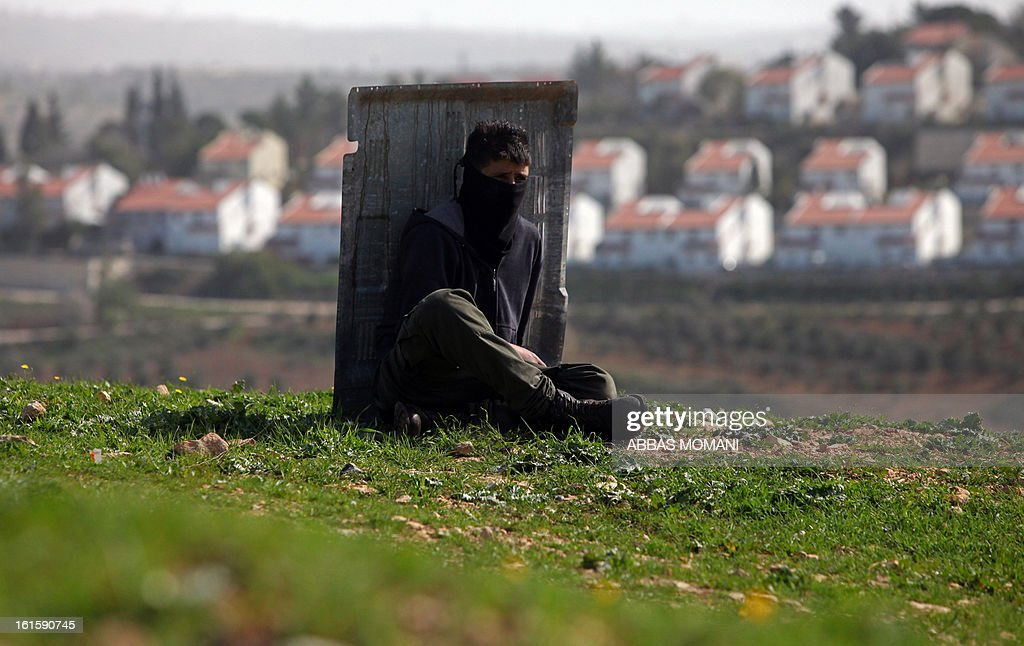 A Palestinian protestor takes cover behind a piece of metal as Israeli soldiers fire tear gas during clashes following a demonstration organised by residents of the West Bank village Nabi Saleh to protest against the expansion of Jewish settlements on Palestinian land on February 8, 2013.