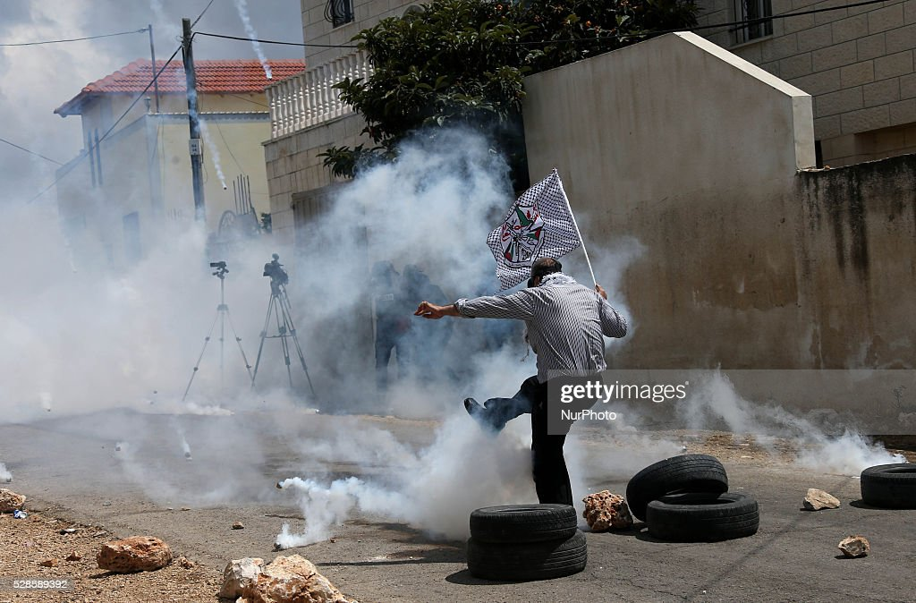 A Palestinian protestor throws back a tear gas canister towards Israeli forces during a protest against the expanding of Jewish settlements in Kufer Qaddom village, near the West Bank city of Nablus. May 6, 2016.