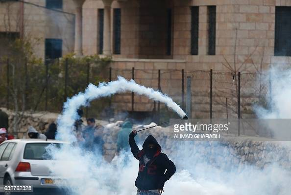 A Palestinian protestor throws back a tear gas canister towards Israeli security forces during clashes following a demonstration demanding that...