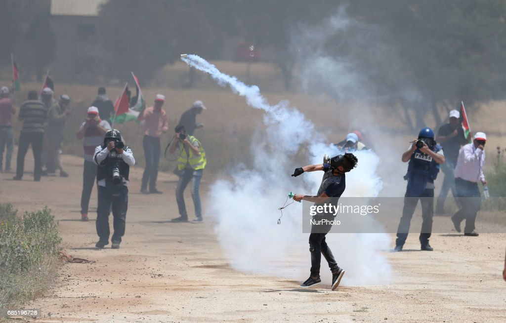 A Palestinian protestor throws back a tear gas canister towards member of the Israeli soldiers during clashes at a protest in support of Palestinian prisoners on hunger strike in Israeli jails, in the West Bank village of Beit Dajan, near Nablus May 19, 2017.