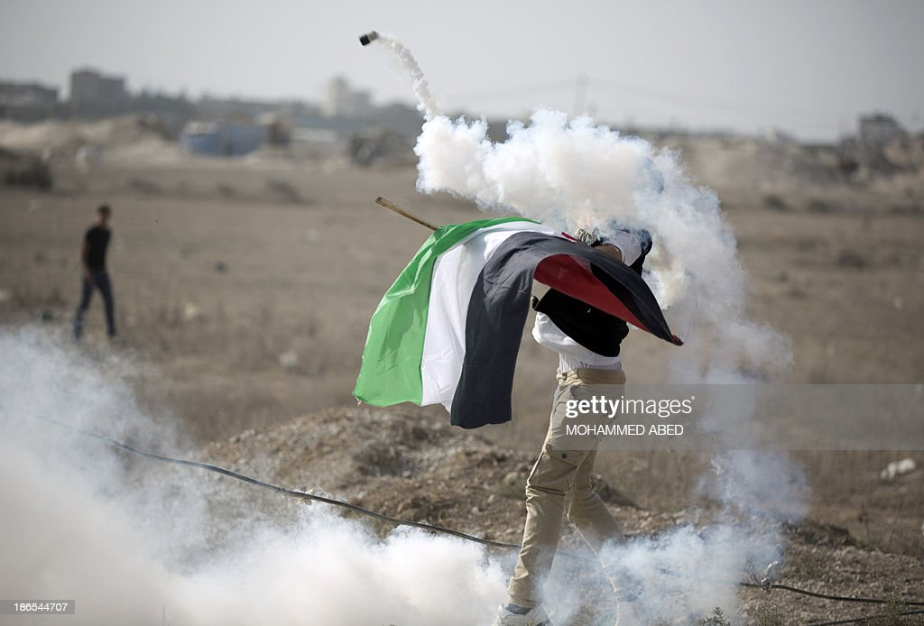 A Palestinian protestor throws back a tear gas grenade fired by Israeli forces during clashes following a protest near the Nahal Oz border crossing with Israel, east of Gaza City, on November 1, 2013. An Israeli raid to destroy a Gaza tunnel ignited clashes in which tank fire killed four Hamas commanders and five Israeli soldiers were wounded, officials from both sides said.