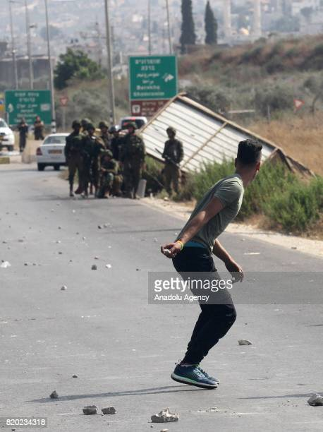 Palestinian protestor throws stones in response to Israeli security forces' intervention with tear gas bomb during a demonstration to protest Israeli...