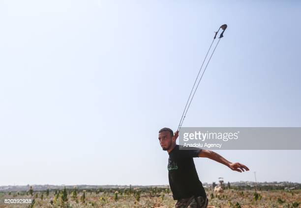Palestinian protestor throws stones in response to Israeli security forces' intervention during a demonstration to protest Israeli violations and...