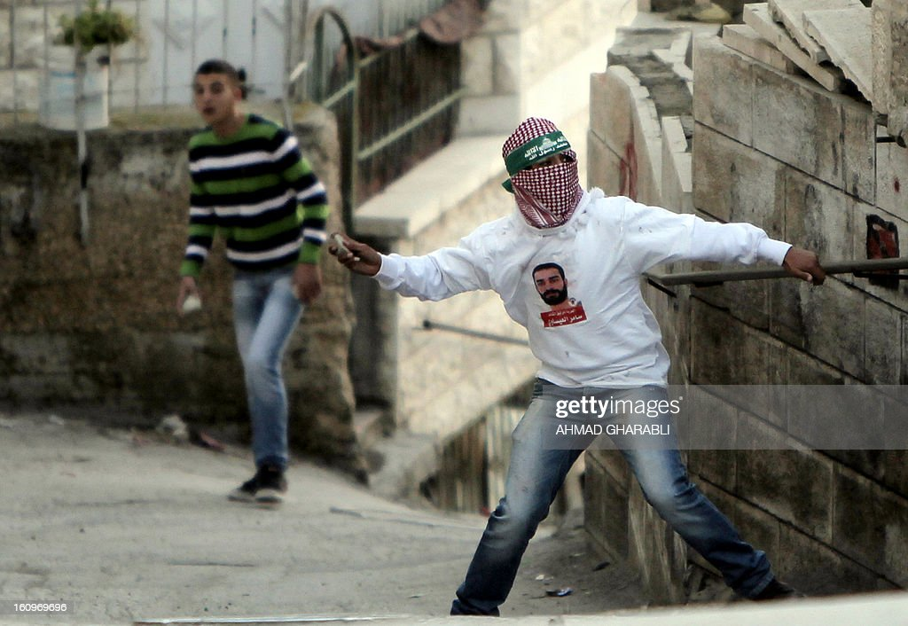 A Palestinian protestor throws stones towards Israeli border guards during clashes in the Arab Jerusalem neighbourhood of Issawiya on February 8, 2013, following a demonstration in solidarity with Palestinian prisoner Samer Issawi (portrait), who is held in an Israeli jail and has been on hunger strike for more than 200 days. Police and border guard forces dispersed the protestors using shock grenades after a number of Palestinian youths hurled rocks at them.