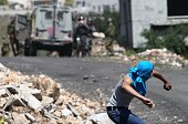A Palestinian protestor throws stones towards Israeli security forces during clashes following a demonstration against the expropriation of...