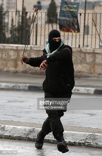 A Palestinian protestor throws stones towards Israeli security forces during clashes following a demonstration demanding that Israeli authorities...
