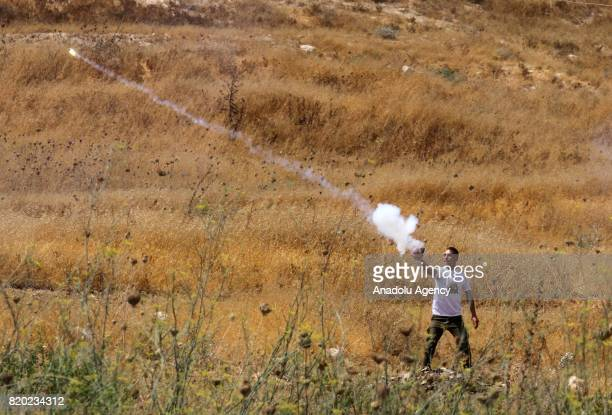 Palestinian protestor uses a firework in response to Israeli security forces' intervention with tear gas bomb during a demonstration to protest...