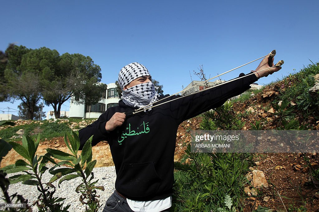 A Palestinian protestor uses a sling shot to throw stones towards Israeli soldiers firing tear gas during clashes following a demonstration organised by residents of the West Bank village Nabi Saleh to protest against the expansion of Jewish settlements on Palestinian land on February 8, 2013. AFP PHOTO/ABBAS MOMANI