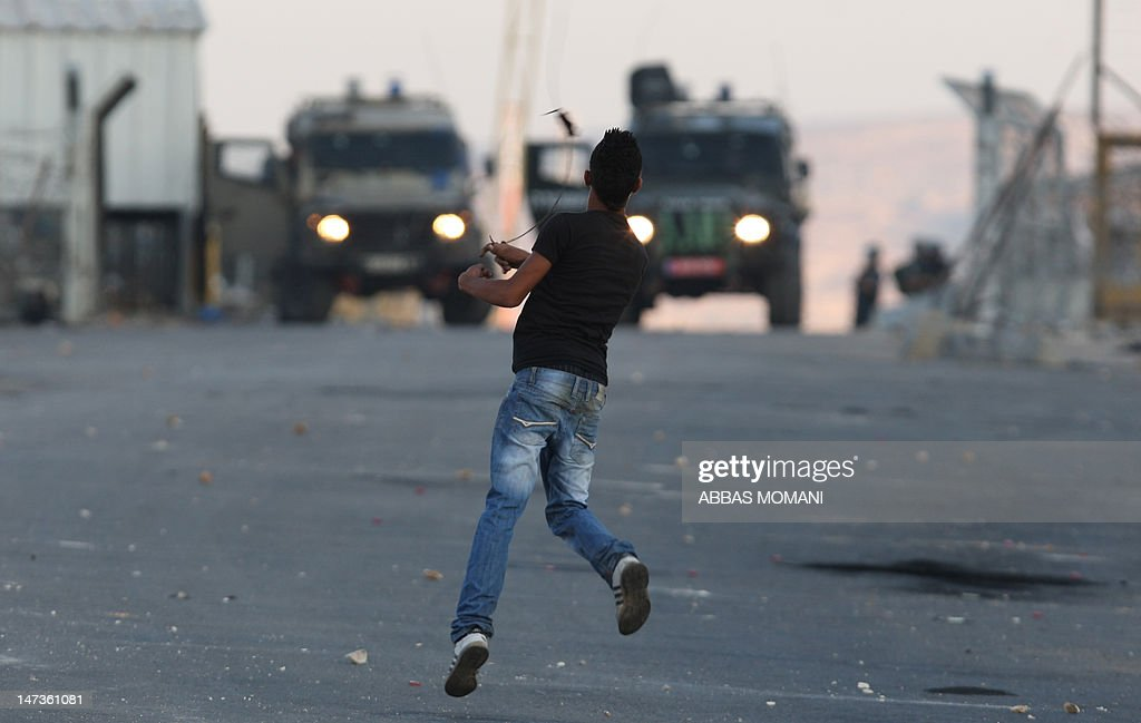 A Palestinian protestor uses a slingshot to throw stones at Israeli army armoured vehicles during clashes following a demonstration on June 28, 2012 outside the Ofer military prison in the occupied West Bank, near Ramallah, in solidarity with Palestinian prisoners being held in Israeli jails. More than 1,500 Palestinian prisoners ended a mass hunger strike in support of demands for better conditions in a deal with prison authorities in May with one of the terms of the agreement being that those held without trial in what Israel calls 'administrative detention' would go free at the end of their current term -- unless fresh evidence emerged against them.