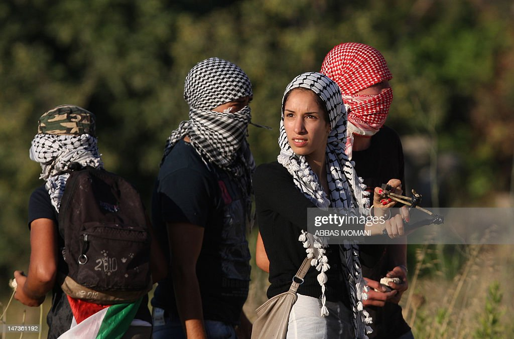 A Palestinian protestor uses a slingshot to throw stones at Israeli troops during clashes following a demonstration on June 28, 2012 outside the Ofer military prison in the occupied West Bank, near Ramallah, in solidarity with Palestinian prisoners being held in Israeli jails. More than 1,500 Palestinian prisoners ended a mass hunger strike in support of demands for better conditions in a deal with prison authorities in May with one of the terms of the agreement being that those held without trial in what Israel calls 'administrative detention' would go free at the end of their current term -- unless fresh evidence emerged against them. AFP PHOTO/ABBAS MOMANI