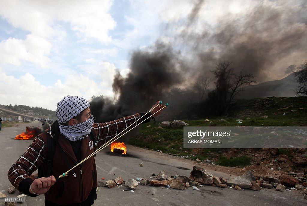 A Palestinian protestor uses a slingshot to throw stones towards Israeli security forces during clashes in front of Ofer prison, near the West Bank city of Ramallah, following a demonstration in support of Palestinian detainee, Samer Issawi, who has been on hunger strike for more than 200 days, and other prisoners on hunger strike in Israeli prisons on February 15, 2013. A United Nations official on February 13, expressed concern about the wellbeing of Palestinian detainees in Israeli prisons and in particular about the condition of Issawi.