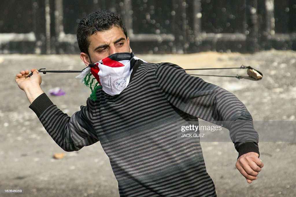 A Palestinian protestor uses a slingshot to throw stones towards Israeli security forces during clashes in the West Bank village of Saair on February 25, 2013 after the funeral of a Palestinian inmate who died in an Israeli prison. Militants of the Al-Aqsa Martyrs Brigades, the armed wing of Palestinian president Mahmud Abbas' Fatah movement, vowed to avenge the death of Arafat Jaradat who they say was tortured in an Israeli jail.