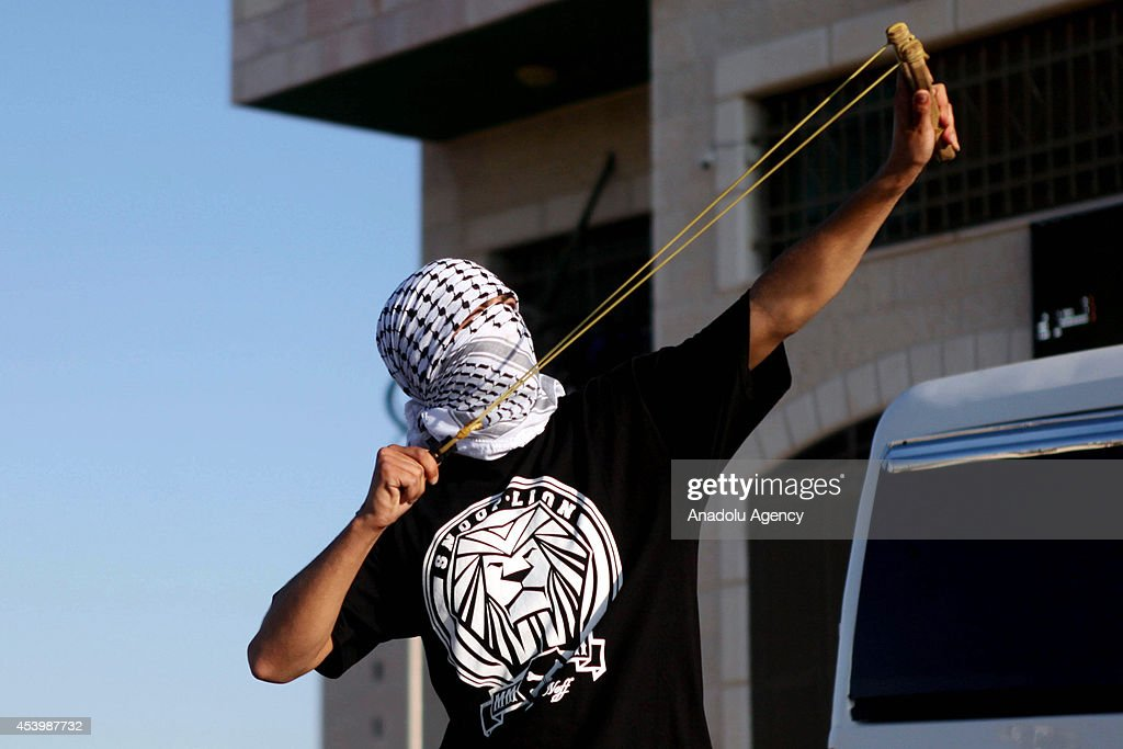 A Palestinian protestor uses sling to throw stone to Israeli soldiers during the protest against the Israeli attacks on Gaza, Silvad village in Ramallah, West Bank on August 22, 2014.