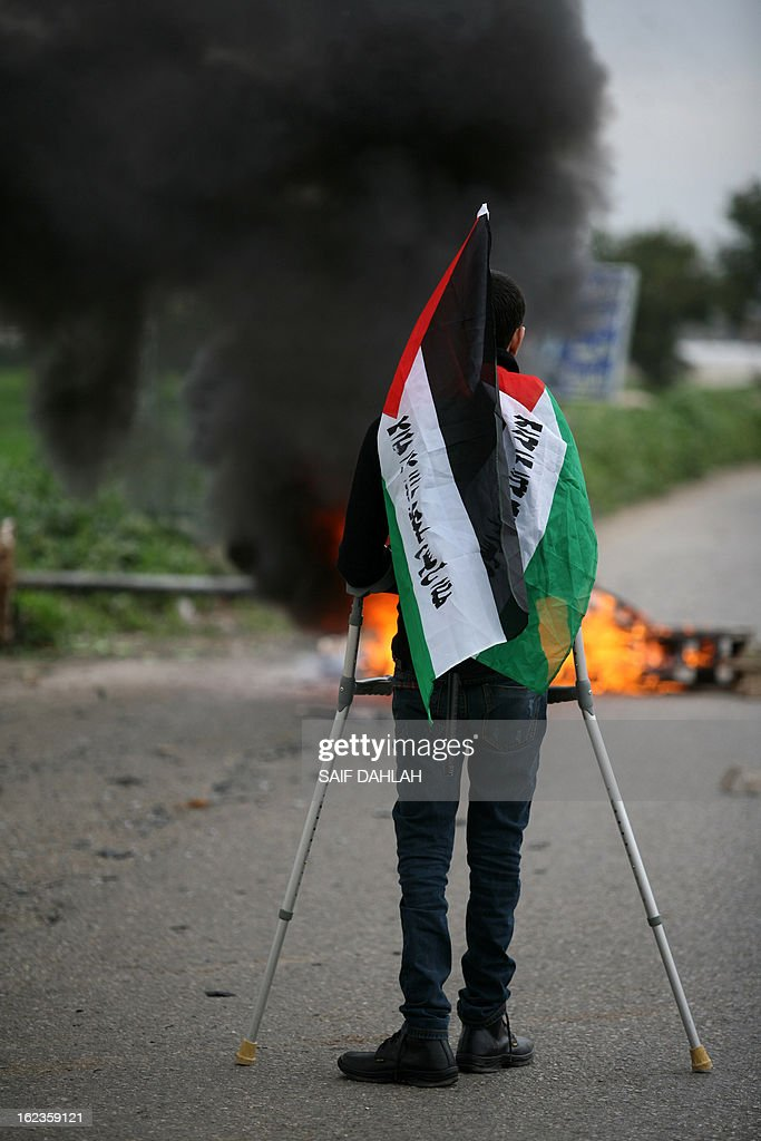 A Palestinian protestor using crutches carries the national flag during clashes with Israeli police at the entrance of the Jalama checkpoint, near the West Bank city of Jenin, on February 22, 2013. Palestinians demanding the release of hunger-striking prisoners clashed with Israelis in the West Bank and east Jerusalem, as three fasting inmates were taken to hospitals. AFP PHOTO/SAIF DAHLAH