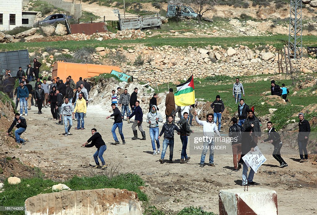 A Palestinian protestor waves his national flag amidst others throwing stones towards Israeli security forces during a demonstration against the closer of the main southwest entrance of the West Bank city of Hebron, which is situated near the Jewish settlement of Beit Hagai, in the occupied West Bank, on February 15, 2013.