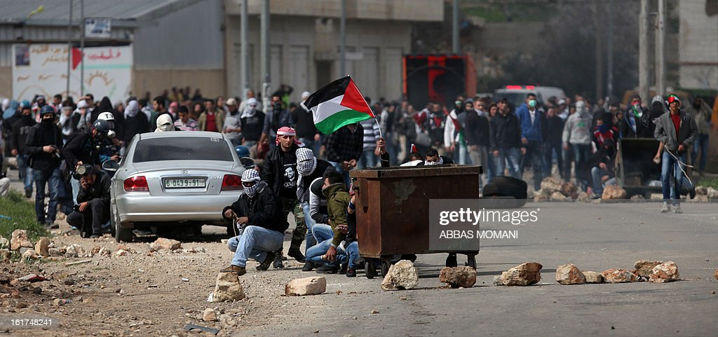 A Palestinian protestor waves his national flag as he takes cover, alongside fellow demonstrators, behind a dust bin during clashes in front of Ofer prison, near the West Bank city of Ramallah, following a protest in support of Palestinian detainee, Samer Issawi, who has been on hunger strike for more than 200 days, and other prisoners on hunger strike in Israeli prisons on February 15, 2013. A United Nations official on February 13, expressed concern about the wellbeing of Palestinian detainees in Israeli prisons and in particular about the condition of Issawi. AFP PHOTO/ABBAS MOMANI