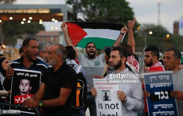 A Palestinian protestor waves his national flag as others hold posters against administrative detention during a demonstration in support of...