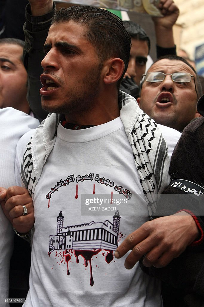 A Palestinian protestor, wearing a shirt to commemorate the Ibrahimi mosque massacre of 1994, chants slogans during a protest demanding the right of access for Palestinians to al-Shuhahda street that can only be used by Israeli settlers in the West Bank town of Hebron on February 22, 2013. AFP PHOTO / HAZEM BADER