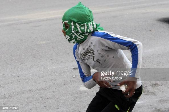 A Palestinian protestor whose face is covered with a Hamas scarf prepares to throw stones towards Israeli security forces during clashes following a...