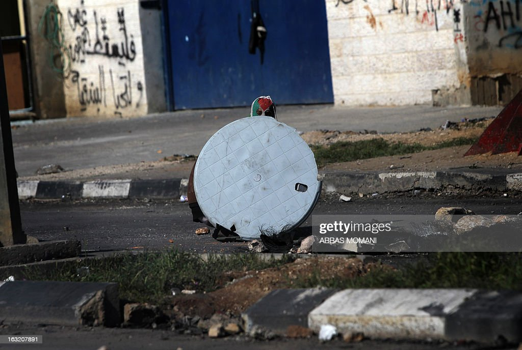 A Palestinian protestor, with his face covered in the colours of his national flag, uses a plastic table as a shield during clashes with Israeli soldiers outside Ofer prison, near Ramallah, following a demonstration in support of Palestinian prisoners on hunger strike in Israeli jails on March 6, 2013. AFP PHOTO/ABBAS MOMANI