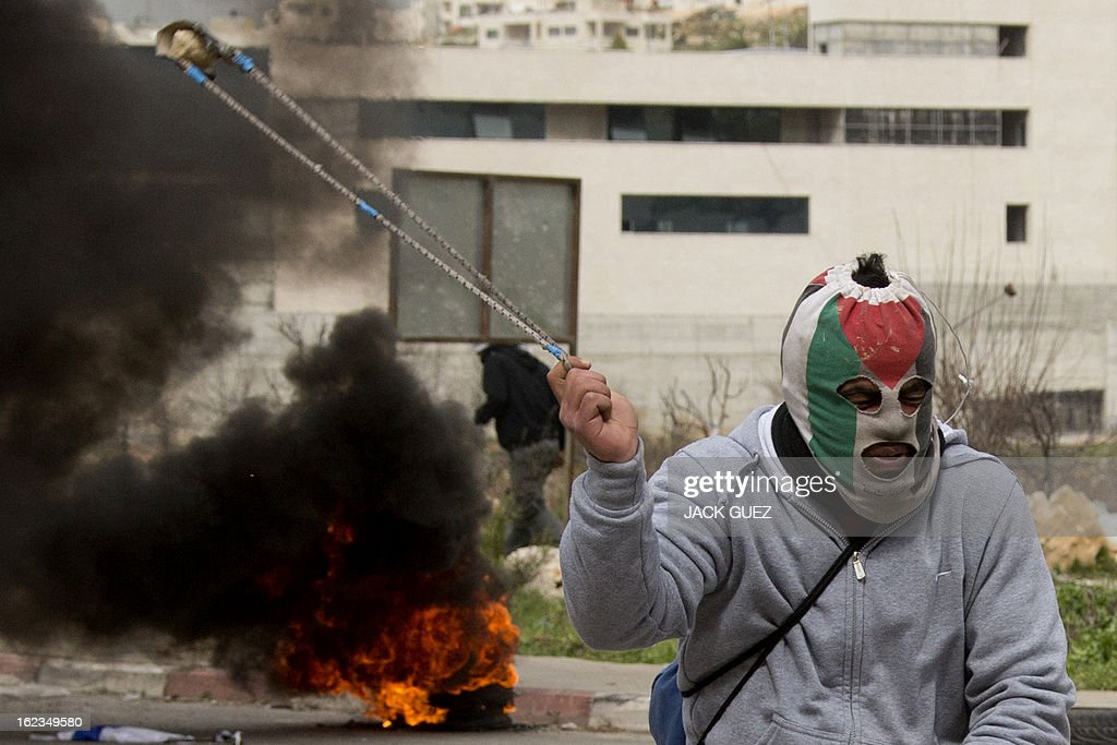 A Palestinian protestor, with his face covered with a mask bearing the colours of his national flag, uses a slingshot to throw stones towards Israeli security forces during clashes next to Ofer prison, near the West Bank city of Ramallah, on February 22, 2013, following a demonstration in support of Palestinian detainees on hunger strike in Israeli prisons. Palestinians demanding the release of hunger-striking prisoners clashed with Israelis in the West Bank and east Jerusalem, as three fasting inmates were taken to hospitals. AFP PHOTO / JACK GUEZ