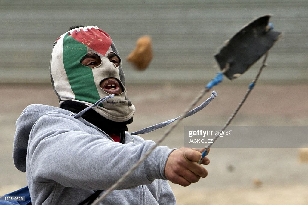 A Palestinian protestor, with his face covered with a mask bearing the colours of his national flag, uses a slingshot to throw stones towards Israeli security forces during clashes next to Ofer prison, near the West Bank city of Ramallah, following a demonstration in support of Palestinian detainees on hunger strike in Israeli prisons on February 22, 2013. Palestinians demanding the release of hunger-striking prisoners clashed with Israelis in the West Bank and east Jerusalem, as three fasting inmates were taken to hospitals. AFP PHOTO / JACK GUEZ