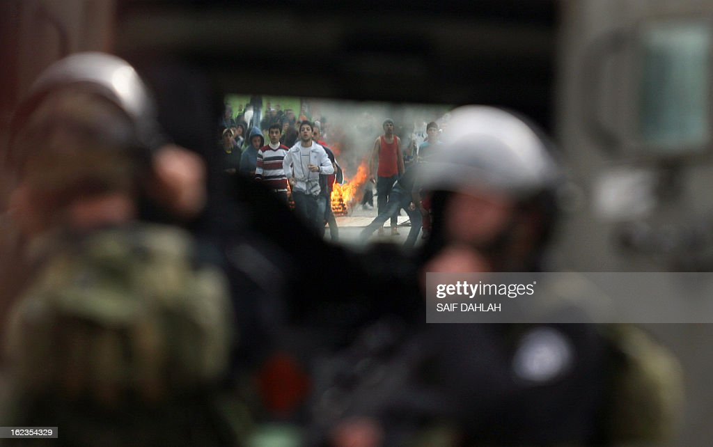 Palestinian protestors are seen through the windshield of an Israeli army vehicle during clashes at the entrance of the Jalama checkpoint, near the West Bank city of Jenin, on February 22, 2013. Palestinians demanding the release of hunger-striking prisoners clashed with Israelis in the West Bank and east Jerusalem, as three fasting inmates were taken to hospitals.