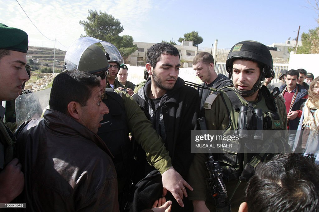 Palestinian protestors argue with Israeli soldiers during a weekly demonstration against Israeli occupation in the West Bank village of Maasarah near Bethlehem on January 25, 2013. The Palestinian leadership wants new dialogue with Israeli political parties, particularly centrists who emerged strong in this week's election, an official said Thursday. AFP PHOTO/MUSA AL S HAER
