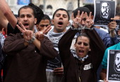 Palestinian protestors chain their hands and flash the sign for victory as they shout slogans during a demonstration in the West Bank city of...