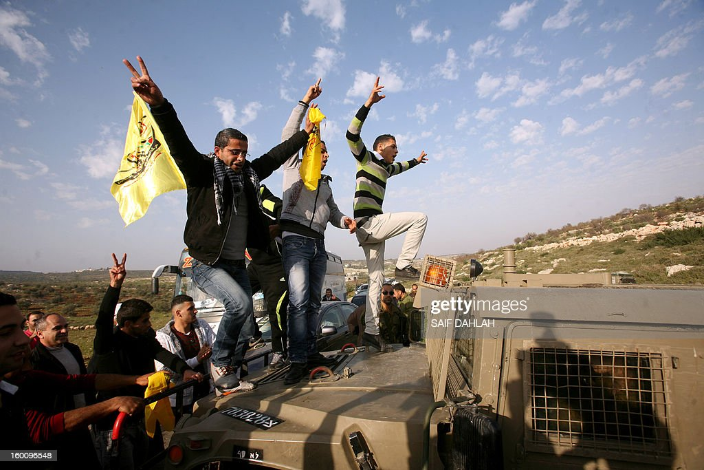 Palestinian protestors climb an Israeli military vehicle during a protest in Anin village in the West Bank near Jenin city, on January 26, 2013. Protestors planned to erect a number of tents in solidarity with Palestinian prisoners in Israeli jails, a move they called 'Breaking the constraint'.