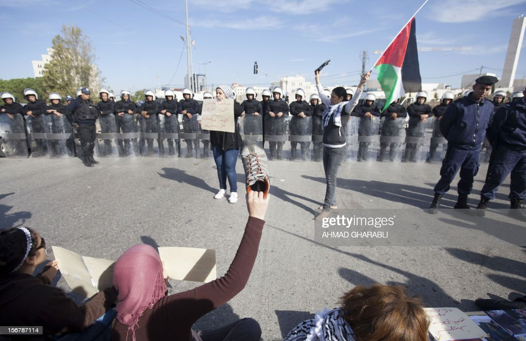 Palestinian protestors confront Palestinian riot police during a demonstration against US Secretary of State Hillary Clinton's visit in the West Bank city of Ramallah on November 21, 2012. US Secretary of State Hillary Clinton expressed 'rock solid' support for Israel's security while calling for a de-escalation of the conflict in Gaza where fighting entered its eighth day, despite signs of an emerging truce.