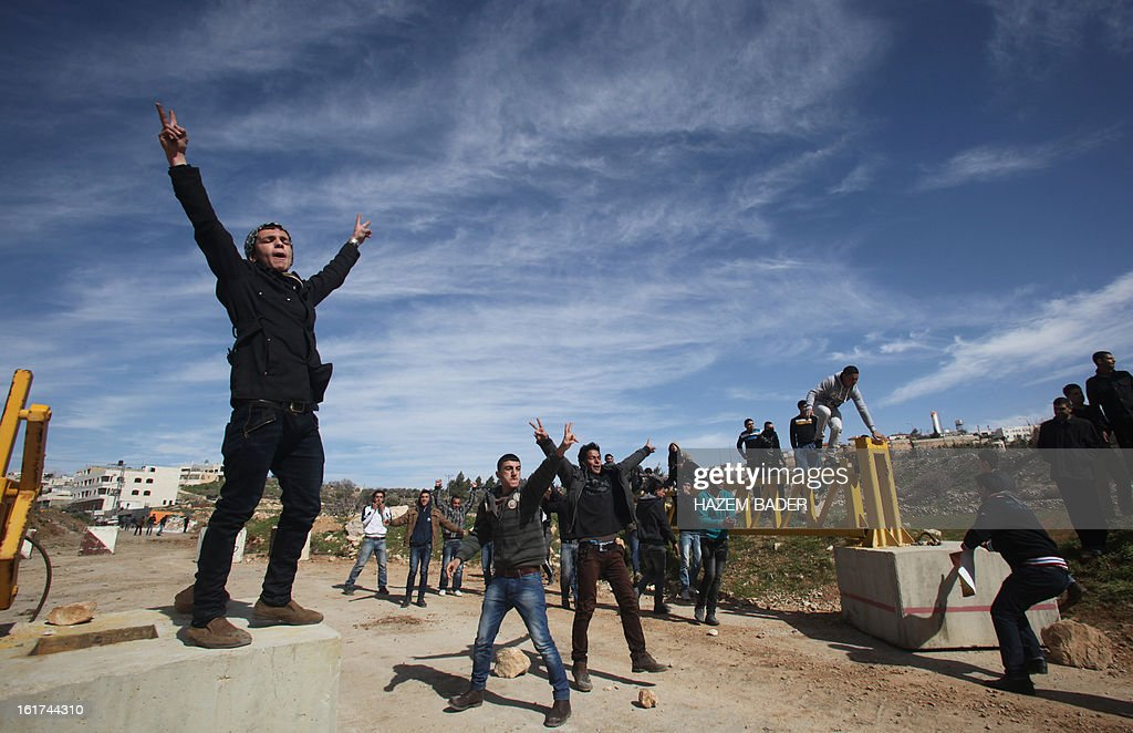 Palestinian protestors flash the sign for victory towards Israeli security forces after opening the gate of the main southwest entrance to the West Bank city of Hebron, during a demonstration against the closer of the entrance to the city, which is situated near the Jewish settlement of Beit Hagai, in the occupied West Bank, on February 15, 2013. AFP PHOTO / HAZEM BADER
