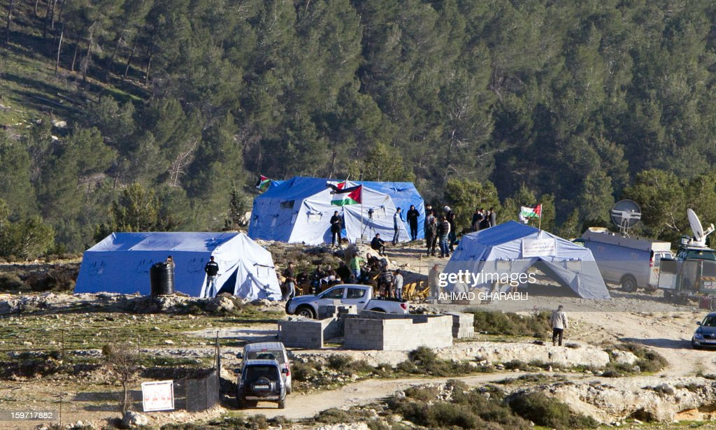 Palestinian protestors gather next to tents erected in the West Bank village of Beit Iksa, between Ramallah and Jerusalem, on January 19, 2013. Some 200 Palestinians gathered at the new encampment protesting for the second consecutive day Israel's intention to confiscate land.