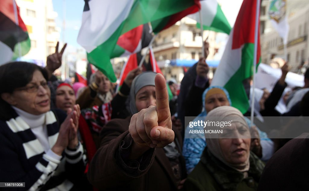 Palestinian protestors gather next to the Muqataa in the West Bank city of Ramallah, on December 27, 2012, in solidarity with the Palestinians in Yarmuk refugee camp in Damascus. Palestinians forced to flee their Damascus camp returned after a reported deal to keep it out of the Syrian conflict.