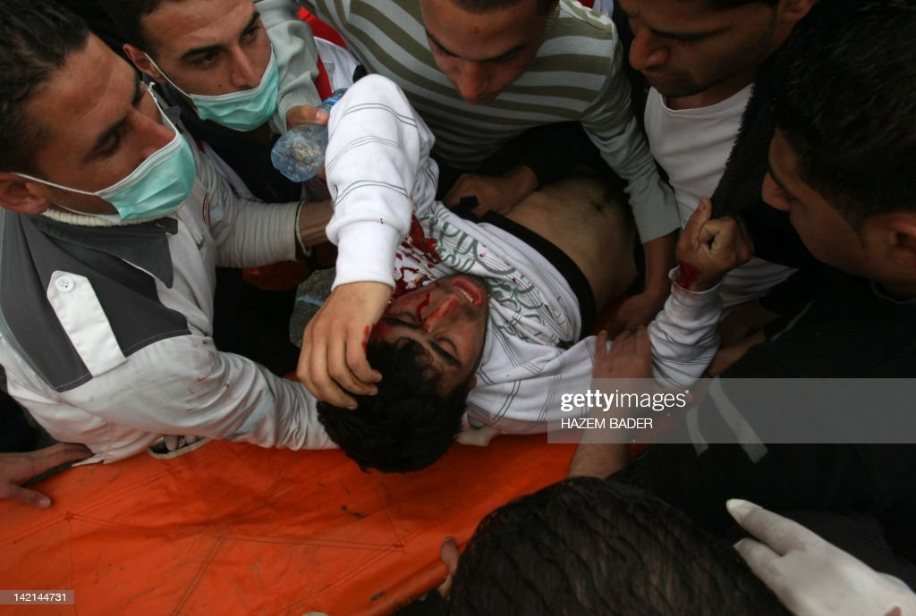 Palestinian protestors help a demonstrator who was hit by a teargas fired by Israeli soldiers during protests at the controversial Israeli separation barrier in the West Bank Jewish settlement of Gilo which lies south of Jerusalem and just north of the West Bank Biblical town of Bethlehem during a demonstration to mark the 'Land day' on March 30, 2012. Hundreds of demonstrators tried to reach the entrance of the separation barrier after Palestinian security forces stopped them. AFP PHOTO/HAZEM BADER