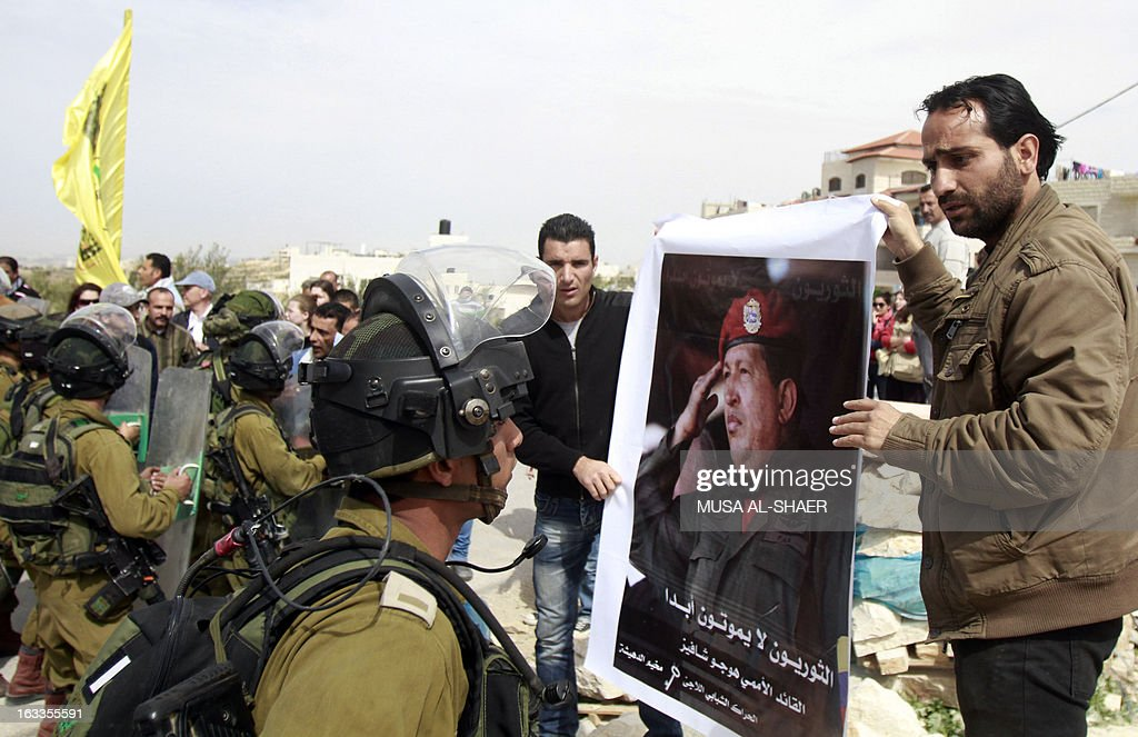 Palestinian protestors hold a picture of late Venezuelan President Hugo Chavez during a weekly demonstration against Israeli occupation in the West Bank village of Maasarah near Bethlehem on March 8, 2013. Palestinians in Gaza and the West Bank were united in grief over the death of Venezuela's Hugo Chavez, whose untiring support for their cause saw him make blistering attacks on Israel. Placard in Arabic reads 'revolutionaries never die.' AFP PHOTO/MUSA AL-SHAER