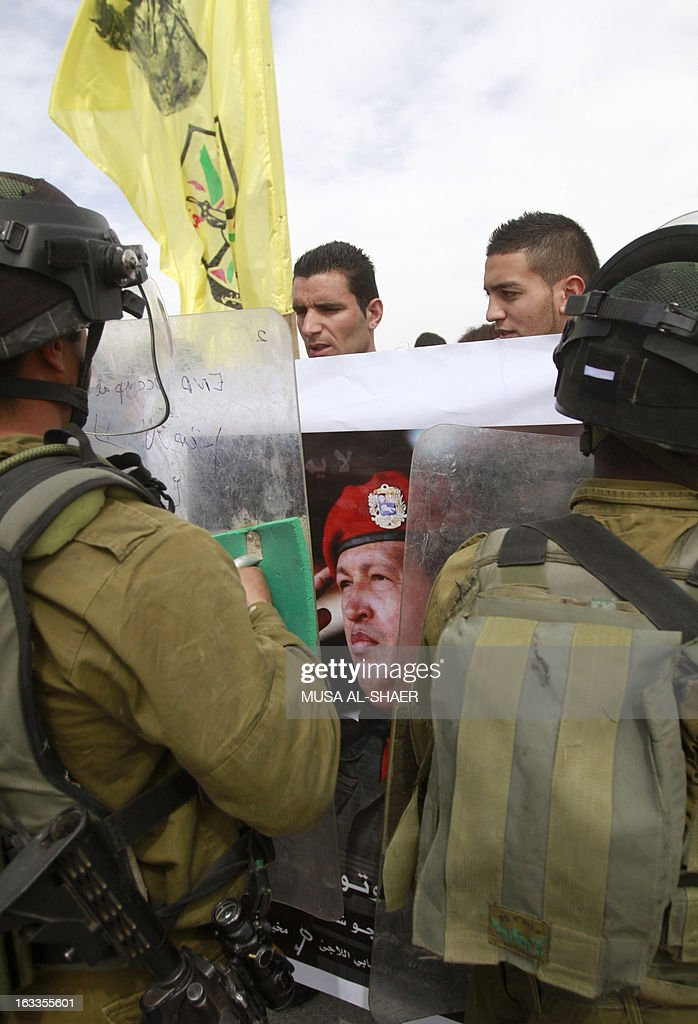 Palestinian protestors hold a picture of late Venezuelan President Hugo Chavez during a weekly demonstration against Israeli occupation in the West Bank village of Maasarah near Bethlehem on March 8, 2013. Palestinians in Gaza and the West Bank were united in grief over the death of Venezuela's Hugo Chavez, whose untiring support for their cause saw him make blistering attacks on Israel.