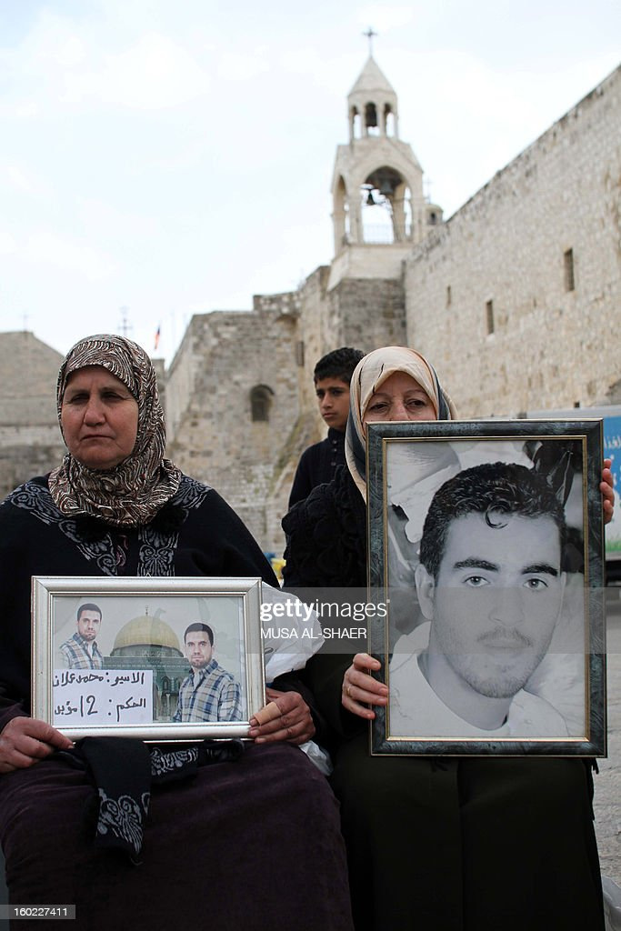 Palestinian protestors hold pictures of detained relatives during a demonstration in support of Palestinians on a hunger strike in Israeli jails, in front of the Church of the Nativity at the West Bank city of Bethlehem on January 28, 2013. AFP PHOTO/MUSA AL-SHAER