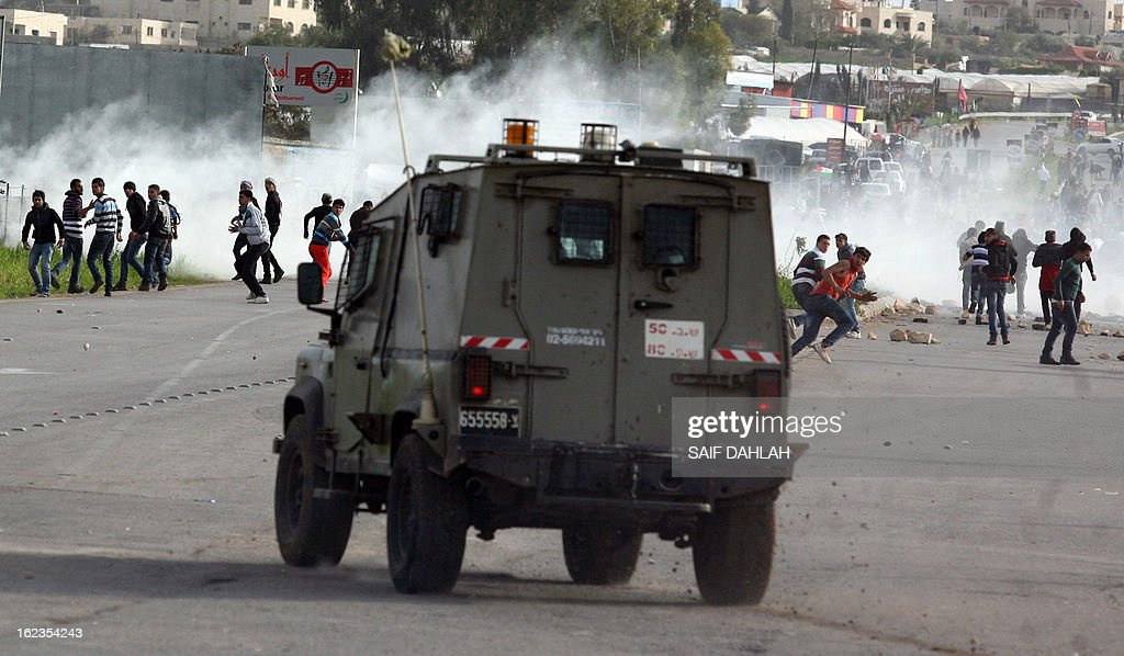 Palestinian protestors hurl stones at Israeli police during clashes at the entrance of the Jalama checkpoint, near the West Bank city of Jenin, on February 22, 2013. Palestinians demanding the release of hunger-striking prisoners clashed with Israelis in the West Bank and east Jerusalem, as three fasting inmates were taken to hospitals. AFP PHOTO/SAIF DAHLAH