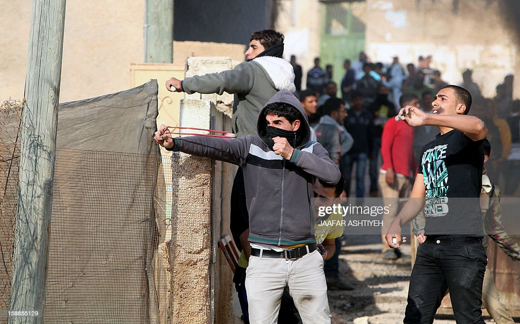 Palestinian protestors hurl stones at Israeli security forces during clashes in the West Bank village of Tamoun, near Jenin on January 1, 2013. Israeli troops wounded dozens of Palestinians in clashes in a West Bank village after the discovery of a small commando force disguised as Arabs brought a crowd of stone-throwing villagers onto the streets, Palestinians said.